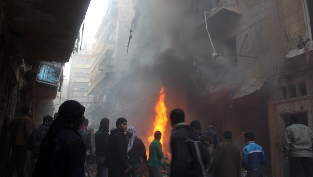 Syrians look at the aftermath of an airstrike on a rebel area of the war-torn northern city of Aleppo