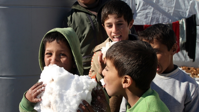 Syrian children play with the snow in the Arsal refugee camp in the Lebanese Bekaa valley