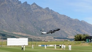 An aeroplane takes off as England's cricketers take on a New Zealand XI in the Remarkables mountain range in Queenstown
