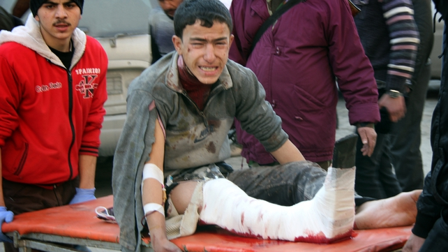 An injured Syrian youth cries as he is carried on a stretcher following an airstrike in the Maadi area of Aleppo