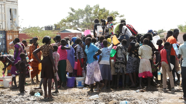 People displaced following recent fighting queue to collect water