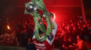 Killian Brennan of St Patrick's Athletic lifts the Airtricity League Premier Division trophy in front the of the Inchicore faithful