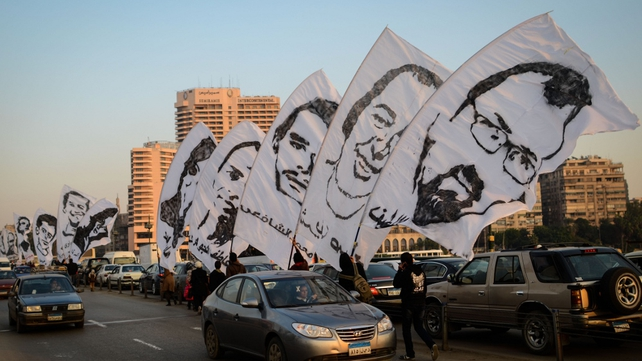 Egyptian protesters hold portraits of people killed last year, as they march in downtown Cairo