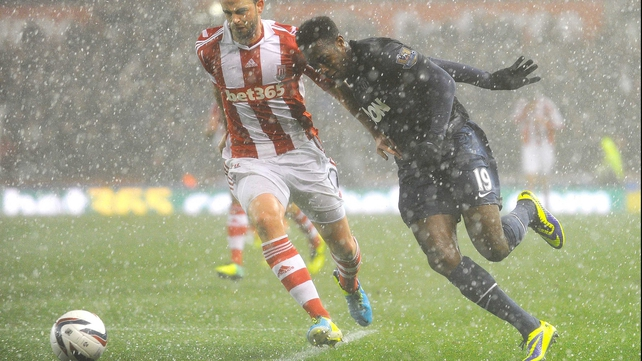 Marc Wilson and Danny Wellbeck challenge for the ball in heavy hail