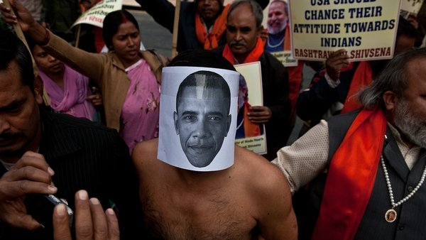 An activist wearing a mask depicting US President Barack Obama takes part in a protest near the US Embassy in New Delhi