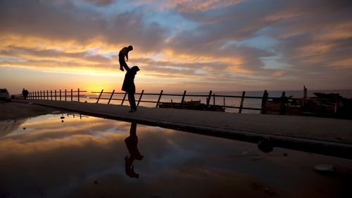 A Palestinian man holding his son up in the air is reflected at sunset in flood waters as he walks along the seafront in Gaza City