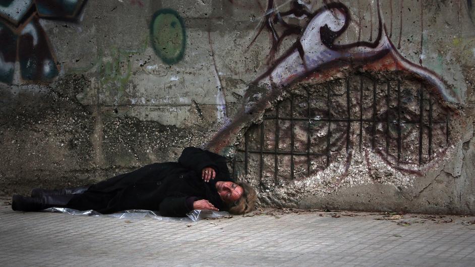 A homeless woman sleeps on a street in the Lebanese capital Beirut