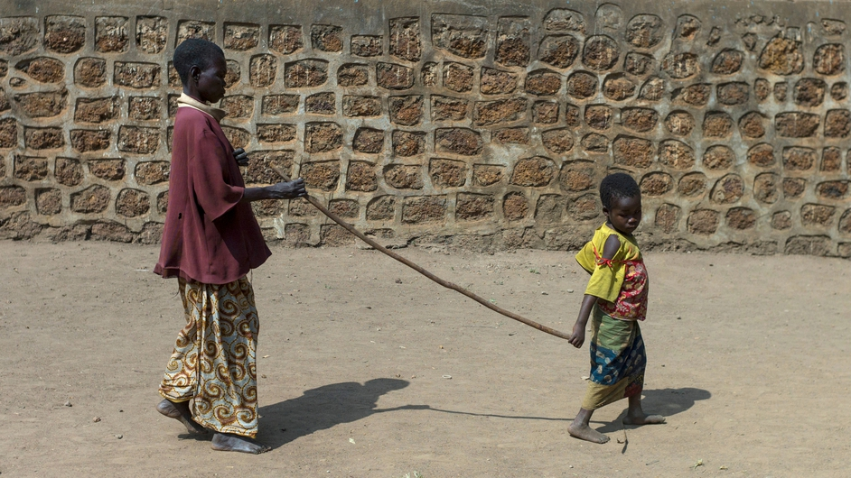 A little girl leads her grandmother with a stick in the Christian refugee camp in Bossangoa, Central African Republic