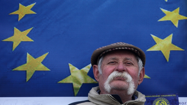 A man stands before an EU flag in Independence Square during a protest rally in Kiev