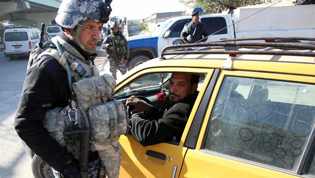 An Iraqi policeman checks a car at a checkpoint in Baghdad