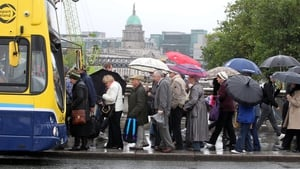 People queue for a bus in the rain in Dublin (Pic: Sam Boal/Photocall)