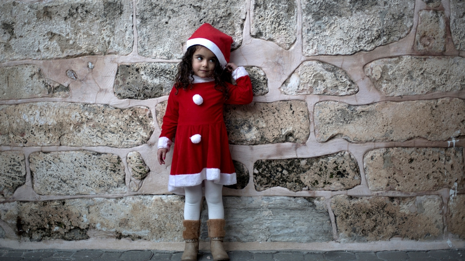 A Palestinian Greek Orthodox Christian girl dressed in Santa Claus stands outside the Saint Porfirios church in Gaza City