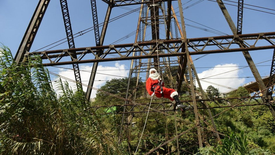 Guatemalan municipal firefighter Carlos Chacon, dressed as Santa Claus, goes down a cable from a bridge to deliver presents to children in Guatemala City