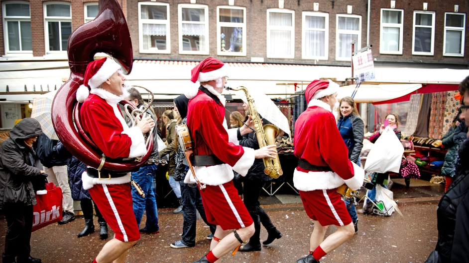 Men dressed as Santa Claus play music at the Albert Cuypmarkt in Amsterdam, the Netherlands