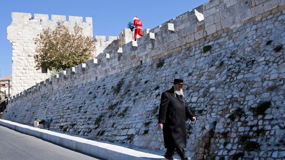 An Ultra-Orthodox Jew walks beneath a Palestinian man dressed up as Santa Claus carrying a Christmas tree and ringing a bell as he walks along the walls of Jerusalem's Old City