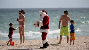 A man dressed as Santa Claus, walks along the beach passing out candy canes and posing for pictures with beach goers in Fort Lauderdale, Florida