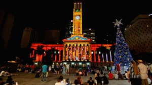People watch a light show in front of a 20m solar-powered Christmas tree in King George's Square in Brisbane, Australia