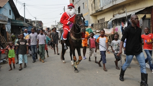 A man wearing a Santa Claus costume rides a horse in a street of Abidjan, Ivory Coast