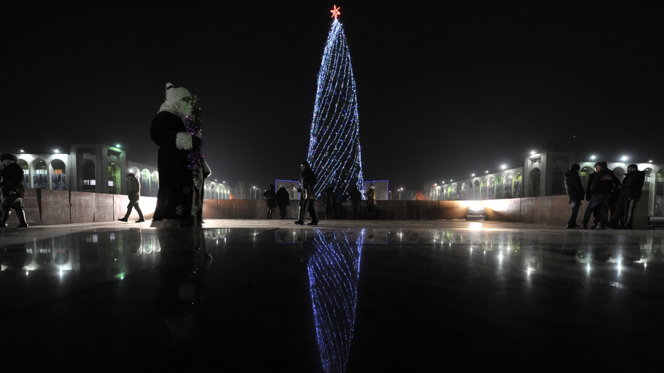 A man wearing costume of Ded Moroz (Grandfather Frost), Russian Santa Claus, stands at the central Ala-Too Square decorated to mark the upcoming New Year holiday in the Kyrgyz capital Bishkek