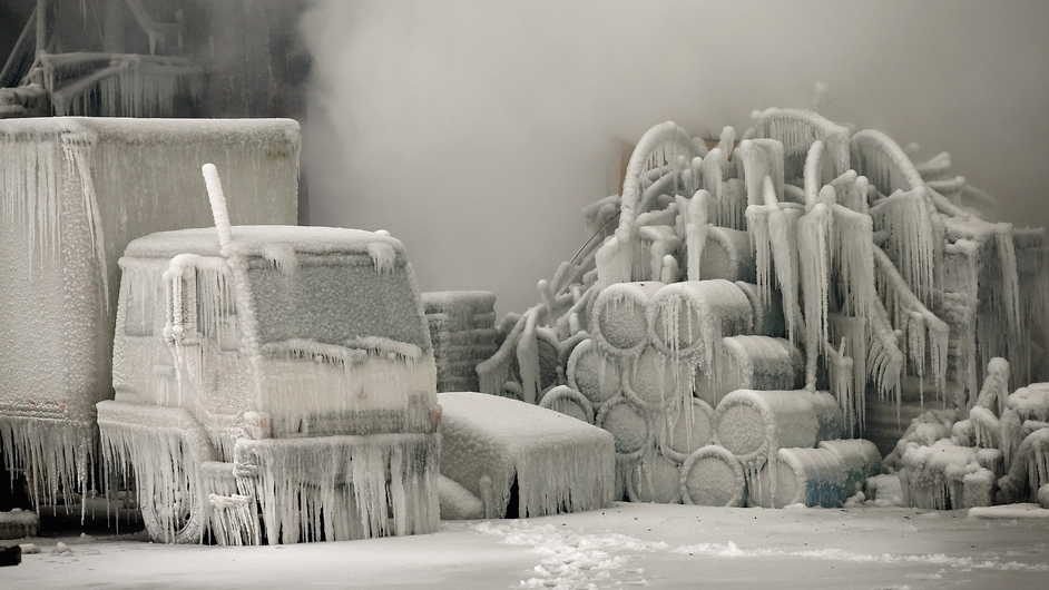 A truck is covered in ice as firefighters help to extinguish a massive blaze at a vacant warehouse in Chicago