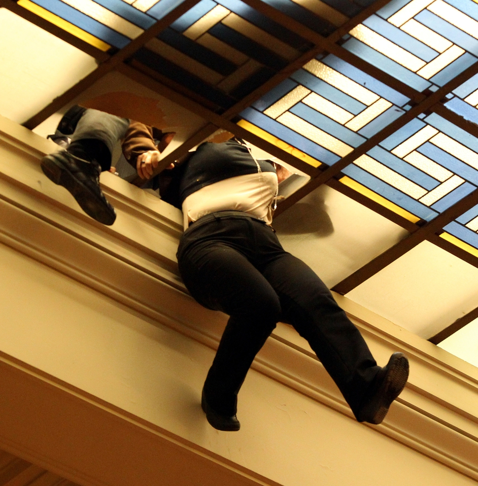 An employee of the Greek Parliament dangles from the roof after falling through the glass at the Greek Parliament Hall