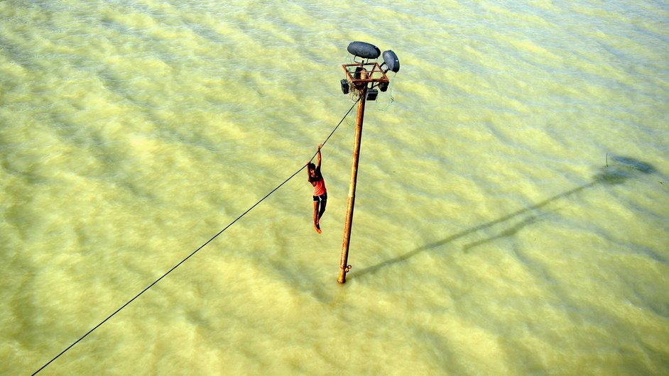 An Indian youth dangles from a power line before diving into the floodwaters of an overflowing Ganges river in Allahabad