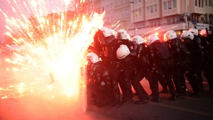 Turkish riot police officers take cover as Kurdish protesters shoot fireworks at them during clashes in central Istanbul