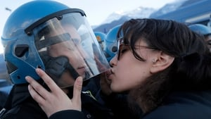 A demonstrator kisses a riot police officer during a protest in Susa against the high-speed train line between Lyon and Turin