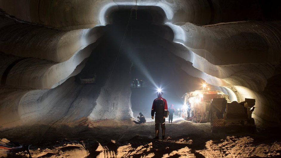 An employee uses the light from a head torch to illuminate the machine cut walls of a potash mine in Berezniki in Russia