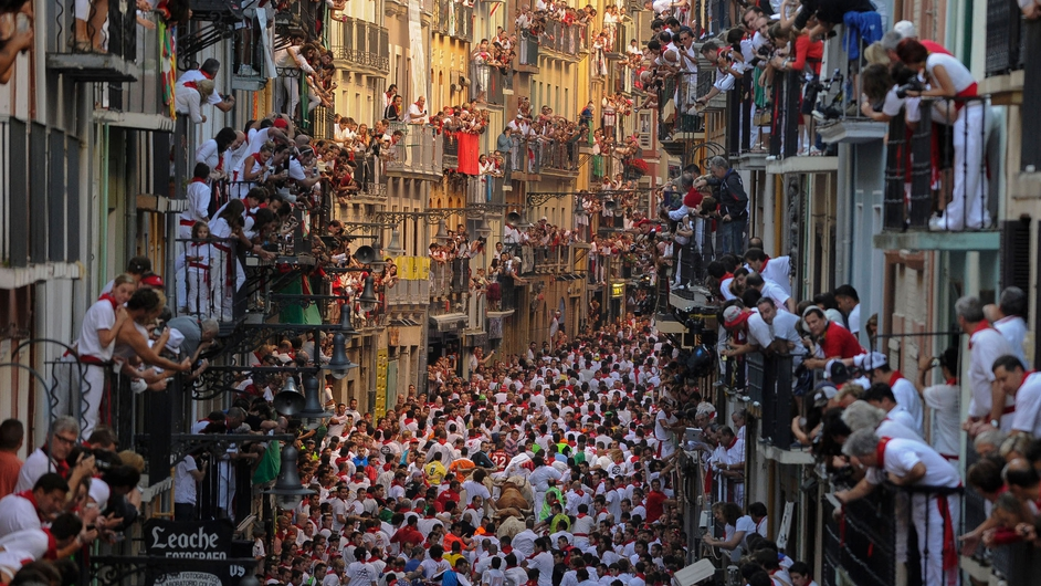 Thousands look at participants as they take part in the bull run in Pamplona, northern Spain
