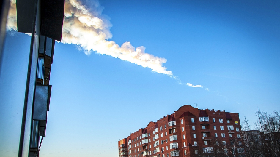 A meteorite trail is seen above a residential apartment block in the Urals city of Chelyabinsk