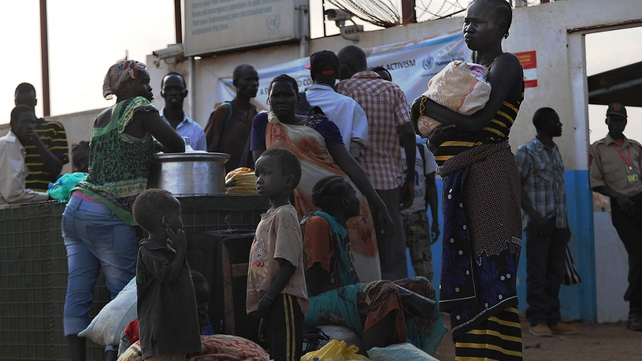 A mother with her children stands with other people seeking refuge at the gates of the UNMISS compound in Juba