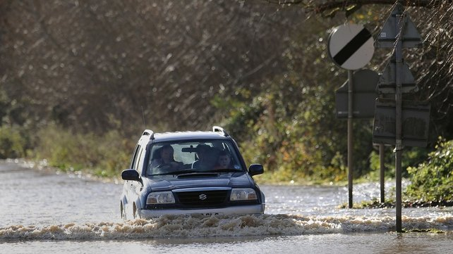 A car makes its way through floodwater in Fladbury, Worcestershire, England
