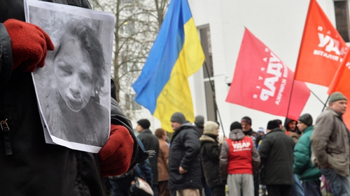 A protester holds a photo showing Tetyana Chornovil's injuries during a picket at the Internal Affairs Ministry in Kiev this morning