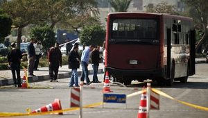 Egyptian security officials inspect the wreckage of a bus damaged by an explosion in Cairo