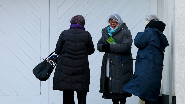 Race card sellers shelter from the wind during day two of the Leopardstown Christmas Festival at Leopardstown Racecourse