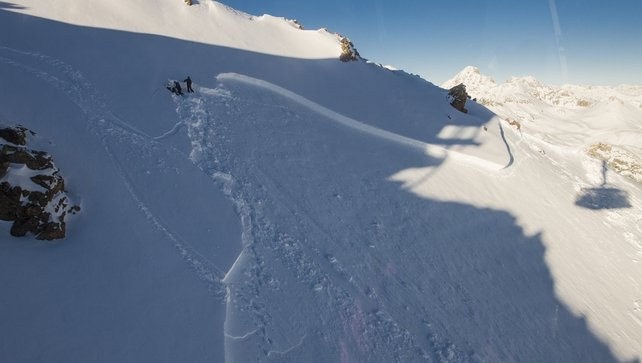 Avalanche experts are seen near the edge of an avalanche in the Swiss Alps