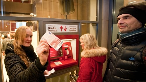 A woman shows a €10 note after withdrawing it from a cash machine in Riga