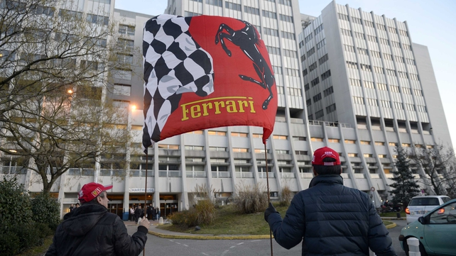 Fans hold a Ferrari flag in front of the Grenoble University Hospital Centre in support of Michael Schumacher