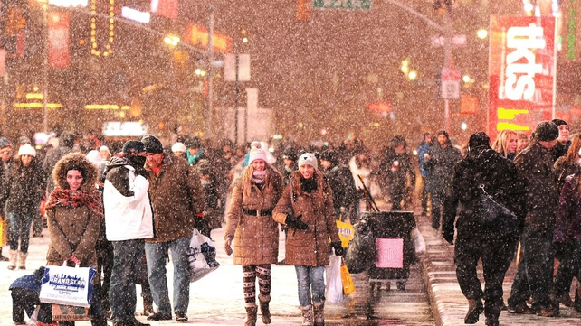 Tourists pose in the snow in Times Square