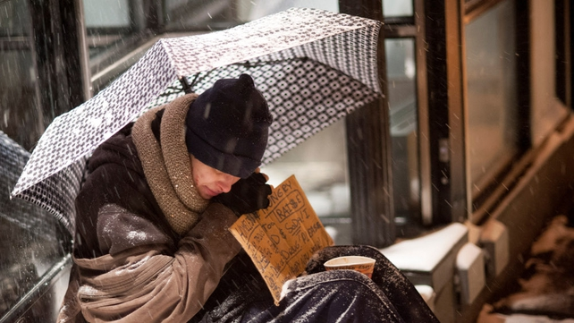 A homeless man seeks shelter under an umbrella as he sits in front of a store in New York