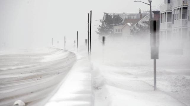 Winds whip snow from the beach across Winthrop Shore Drive in Winthrop, Massachusetts