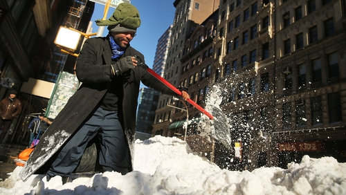 Diego Ramos, who is homeless and lives under nearby building scaffolding, clears a sidewalk of snow in lower Manhattan