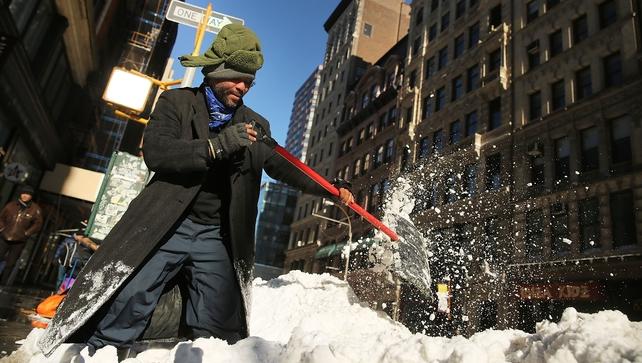 A man clears a sidewalk of snow in lower Manhattan