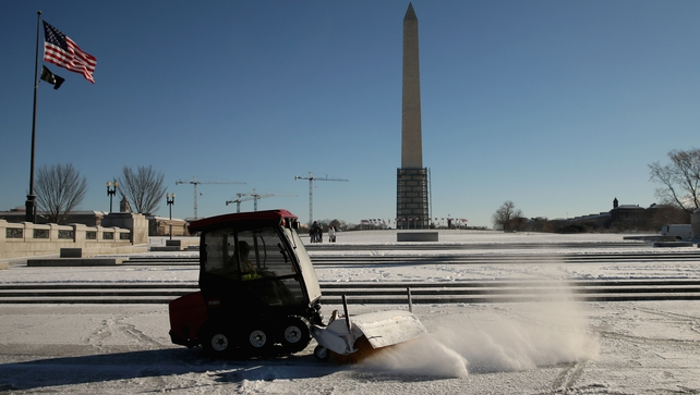 A US Park Service snowplough works to clear snow and ice from the World War II Memorial in Washington,