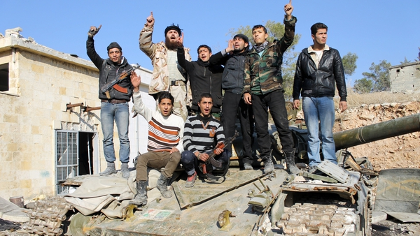 Rebel fighters stand on top of a tank confiscated from pro-regime fighters in the northern Syrian city of Aleppo on 21 December