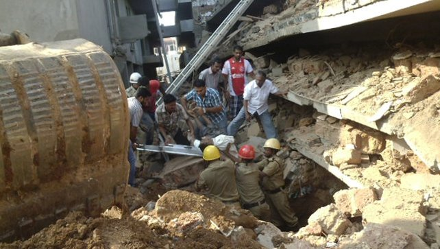 Rescue workers pull a victim from the rubble of a collapsed building in Goa