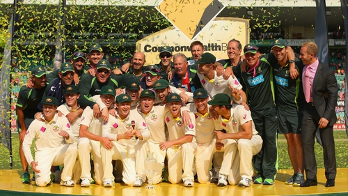 The Australian team and support staff celebrate with the Ashes urn