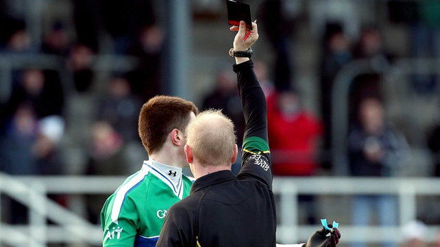 Athlone IT's Jack Donoghue is shown a black card by referee Derek Fahy