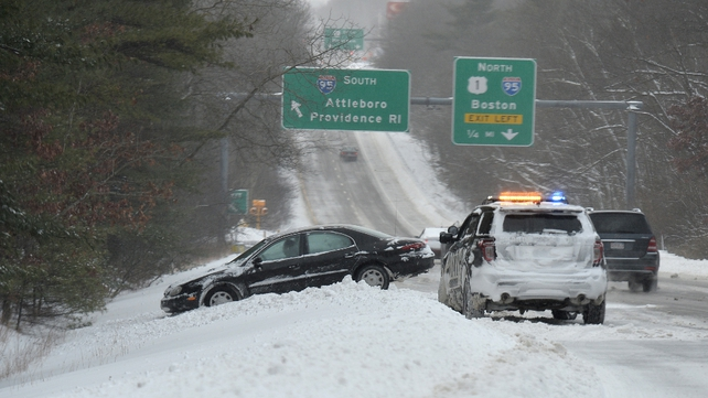 A police officer assists a driver who slid off the roadway along Southbound Route 1 at the I95 interchange in Sharon, Massachusetts